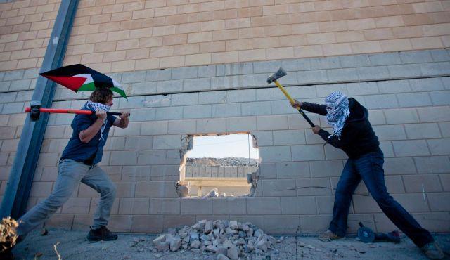 Palesztin aktivisták egy lyukat vágva emlékeznek meg a berlini fal leomlásának 25. évfordulójáról. Bir Nabala, 2014.11.08. Fotó: AP, Forrás: Haaretz