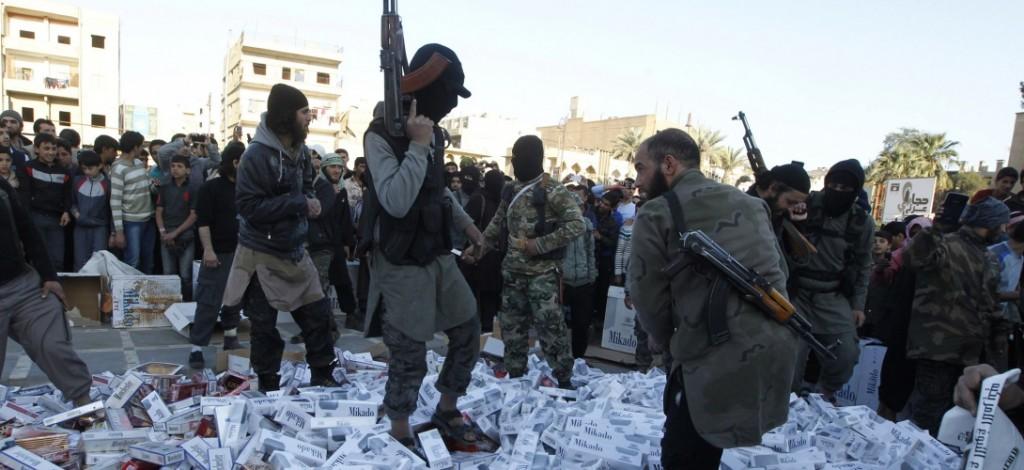 2014 áprilisában Rakkában az akkor még az Iraki és Levantei Iszlám állam (ISIS) néven futó szervezet tagjai elkobzott cigarettakartonokon taposnak. Fotó: Reuters; slate.fr
