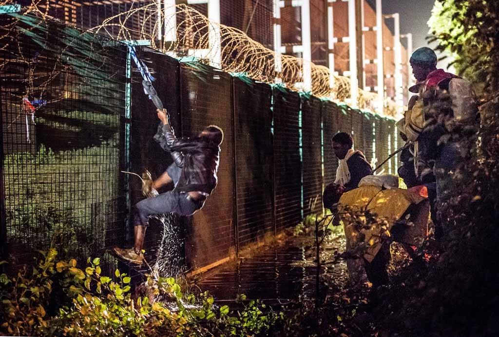 Átkelési kísérlet az Eurotunnel kerítésén, Coquelles-ben, Calais közelében 2015. július 30-án; Fotó: AFP / PHILIPPE HUGUEN
