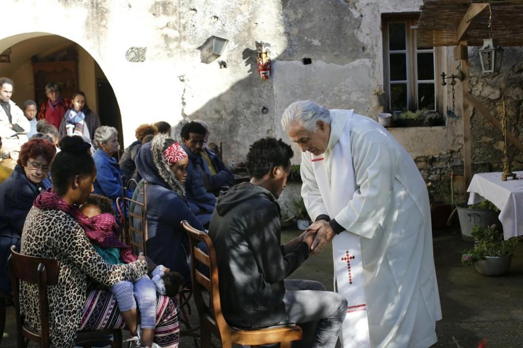 Vallási szertartás Francois Cotta házánál, a pap éppen Meabelt vigasztalja, aki most értesült róla, hogy felesége nem élte túl a Földközi-tengeren való átkelést. Fotó: Laurent Carré, Libération