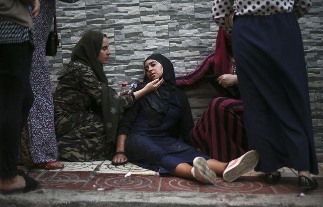 Az egyik tüntetőt rosszullét miatt ápolják - a környék lakosai több esetben is Coca-Colával próbálták enyhíteni a könnygáz negatív hatásait; fotó: Teresa di Campo/AP, forrás