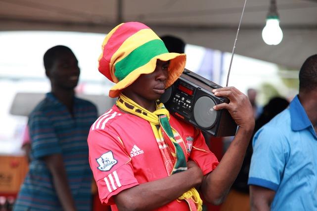 Egy ghánai szurkoló rádión hallgatja a válogatott meccs kommentálását, Accrában, 2014 június 26-án.