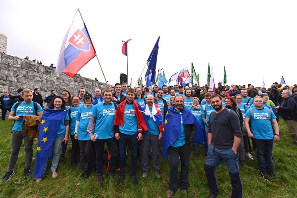 A vezető képen a Progresszív Szlovákia küldöttségét látják Milan Rastislav Štefánik csehszlovák politikus síremléke előtt 2019 május 4-én. A háttérben a Néppárt - Mi Szlovákiánk párt zöld zászlói. Fotó: Halász Photography, Facebook.