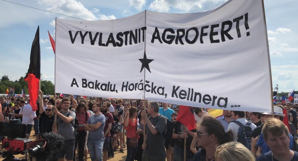 """A képen baloldali tüntetől egy """"Kobozzuk el az Agrofertet!"""" feliratú transzparenssel jelentek meg a nyári Letna parki demonstráción, 2019 júniusban. Fotó: a2larm.cz."""