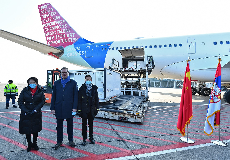 Vezető képünkön Aleksandar Vučić Szerbia elnöke és a Chen Bo szerbiai kínai nagykövet pózol fotósoknak az egymillió kínai vakcina szállítmánnyal percekkel korábban landoló Air Serbia repülőgépe előtt. Forrás:
