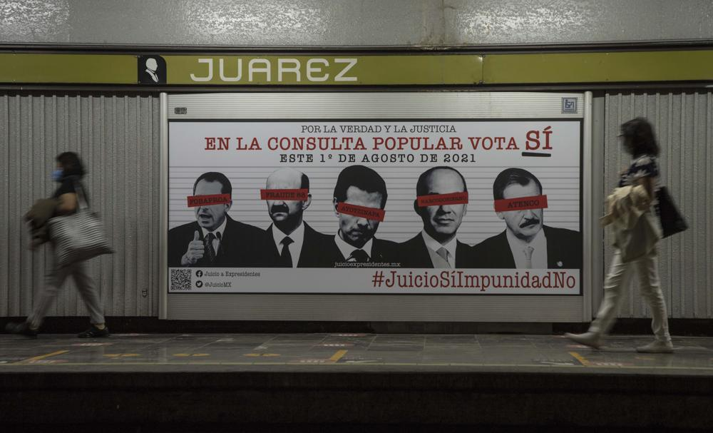 Városlakók haladnak el Mexikóváros Juarez negyedében kitett nemzeti konzultációt hirdető óriásplakát előtt 2021 július 31-én. Az eldöntető kérdést feltett népszavazás körülbelül 25 millió dollárba kerül a mexikói költségvetés számára. Kép forrása: Twitter.